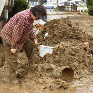 Image: A woman removes mud from her house following heavy flooding in Asakura