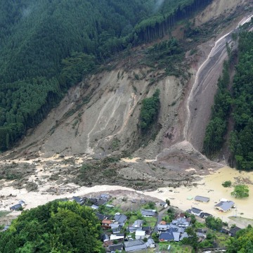 Image: Houses and a road are seen submerged in muddy water after a huge landslide caused by heavy rain