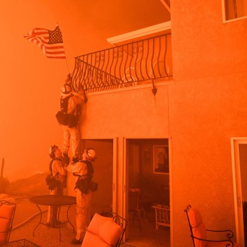 """Image: Firefighters remove a U.S. flag as flames from the """"Wall Fire"""" close in on a luxury home in Oroville, California"""