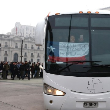 """Image: A woman holds a national flag with the words """"No to transgender ideology, more family, less state"""" while riding on a bus of conservative advocacy group Citizen Go in Santiago"""