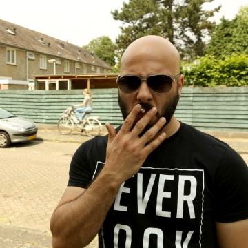 Image: Saflou smokes a cigarette outside his new apartment