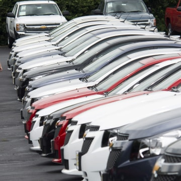 Image: People browse through rows of cars for sale at a car dealership in Columbus, Ohio.