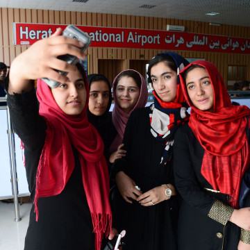 Image: Afghan teenagers from the Afghanistan Robotic House take pictures with a mobile phone at Herat International Airport.