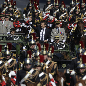 Image: French President Emmanuel Macron and Chief of the Defense Staff Gen. Pierre de Villiers, drive down the Champs Elysees avenue during Bastille Day