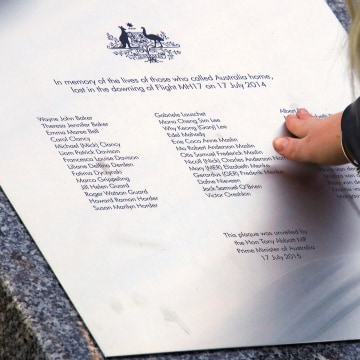 Image: A relative of an Australian victim of Malaysia Airlines jet MH17 touches a memorial that was unveiled outside Parliament House in Canberra, Australia, July 17, 2017.