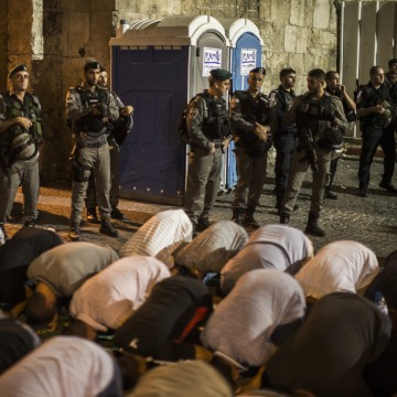 Image: Some 4,000 Muslims pray outside the entrance to the Old City of Jerusalem as it is partially blocked by Israeli police.
