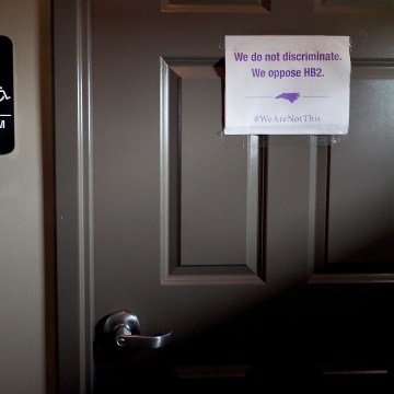 "Image: A unisex sign and the ""We Are Not This"" slogan are outside a bathroom."