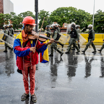 Image: An opposition demonstrator plays the violin during a protest against President Nicolas Maduro in Caracas, on May 24, 2017.