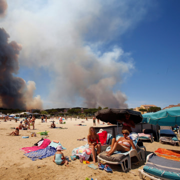 Image: Smoke fills the sky above a burning hillside as tourists relax on the beach in Bormes-les-Mimosas