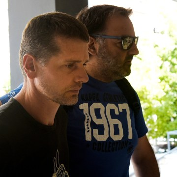 Image: Alexander Vinnik, a Russian man suspected of running a money laundering operation, is escorted by a plain-clothes police officer to a court in Thessaloniki