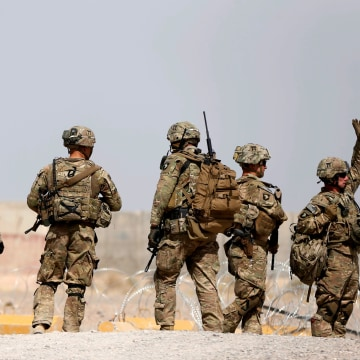 Image: U.S. troops walk outside their base in Uruzgan province
