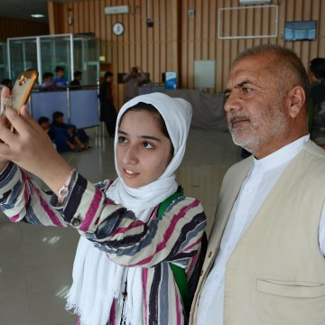 Image: Afghan teenager Fatemah Qaderyan takes a photograph with her father at Herat International Airport