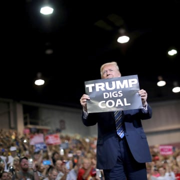 Image: U.S. President Donald Trump holds a sign as he arrives at a rally in Huntington, West Virginia