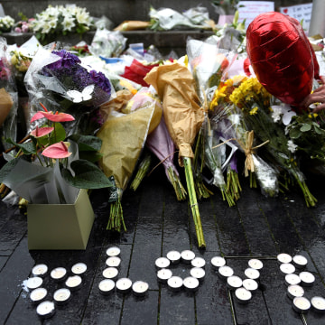 Image: A person lays a floral tribute after a vigil