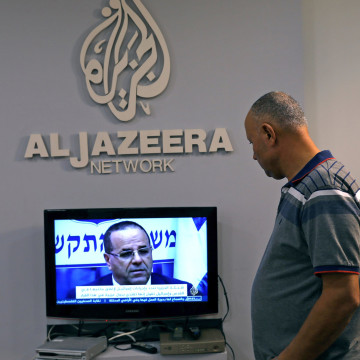 Image: An employee working inside the office of Qatar-based Al-Jazeera network in Jerusalem