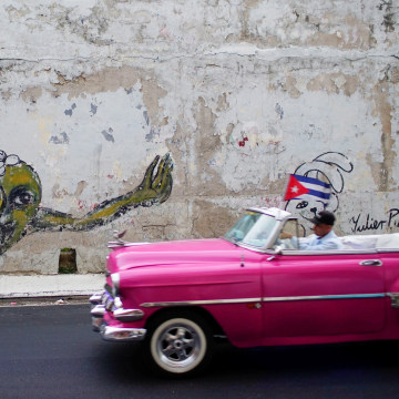 Image: A vintage car passes by a graffiti of Cuban Artist Yulier Rodriguez in Havana, Cuba