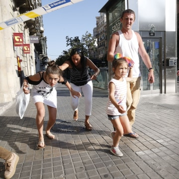 Image: People leave a cordoned off area after a van plowed through a crowded pedestrian plaza in Barcelona