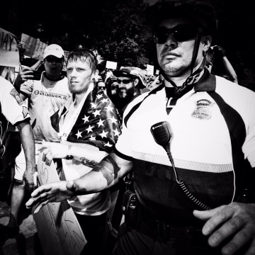 Image: A 'Free Speech Rally' attendee is ushered through the crowd of protesters by police.