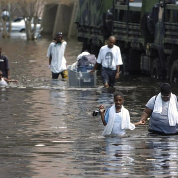 Image: People wade through floodwaters on their way to the Superdome in New Orleans looking for shelter