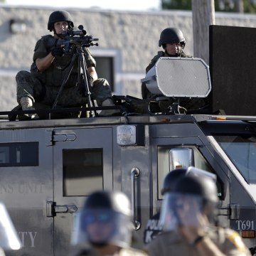 Image: A police tactical team moves in to disperse a group of protesters in Ferguson