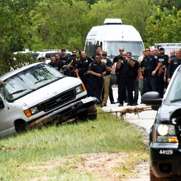Image: Police investigators watch as the van containing the six members of the the Saldivar family who died is towed to the road