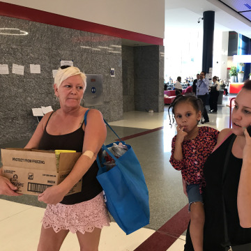 Image: Madison Gingrow, 21, holds her daughter Aleiyah, 3, and walks with her mom, Rene Farrell, 50, right, at the George R. Brown Convention Center as they try to find funds to relocate after Hurricane Harvey, Sept. 1, 2017.