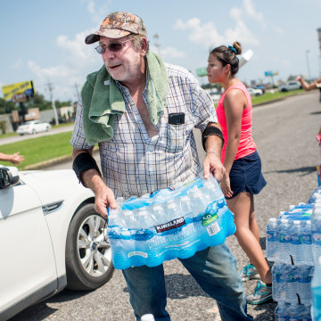 Image: Volunteers help load Harvey victims cars with donated supplies