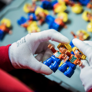 Image: An employee performs a quality control inspection on Lego Duplo figurines