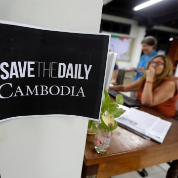 Image: Journalists work at the newsroom of The Cambodia Daily newspaper in Phnom Penh