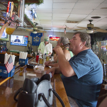 Image: Linda Pauly tops off another pitcher of beer in Gator's Crossroads, a dive bar along U.S. 41 in Collier County, Florida.