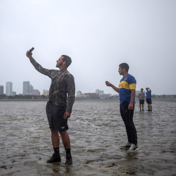 Image: The Tampa skyline is seen in the background as local residents  Rony Ordonez, left, Jean Dejesus and Henry Gallego take photographs after walking into Hillsborough Bay while awaiting the hurricane's arrival in Tampa on Sept. 10.