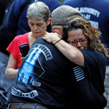 Image: People embrace as they gather at the National 911 Memorial and Museum during ceremonies marking the 16th anniversary of the September 11, 2001 attacks in New York