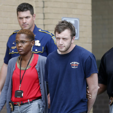 Image: Kenneth James Gleason is escorted by police to a waiting police car in Baton Rouge