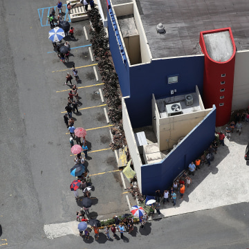 Image: People wait in a long line at a bank aftermath of Hurricane Maria