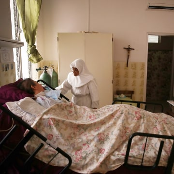Image: Sister Gloria Flores checks in on a  patient at the Hermanitas de los Ancianos Desamparados facility which cares for the elderly