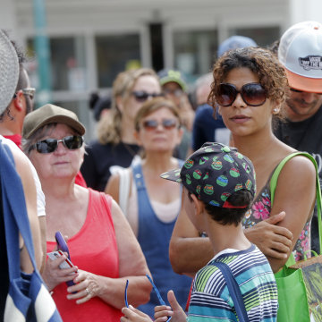 Image: People wait in line to withdraw cash at a bank in San Juan