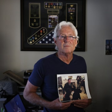 """Image: William Owens holds a photo of his youngest son Navy SEAL William """"Ryan"""" Owens in Lauderdale by the Sea, Florida."""