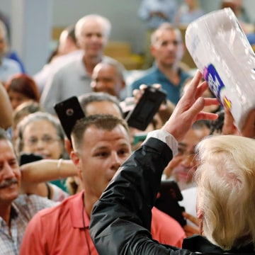 Image: U.S. President Donald Trump throws rolls of paper towels to a crowd of local residents