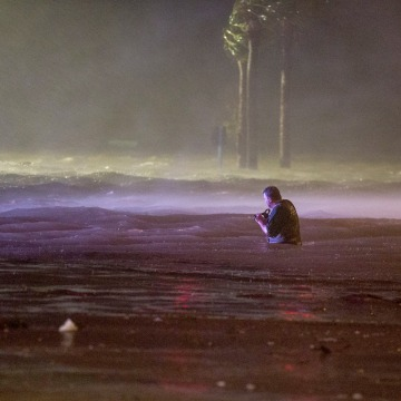 Image: Lanny Dean, from Tulsa, Oklahoma, takes video as he wades along a flooded Beach Boulevard next to Harrahs Casino as the eye of Hurricane Nate pushes ashore in Biloxi, Mississippi on Oct. 8, 2017.