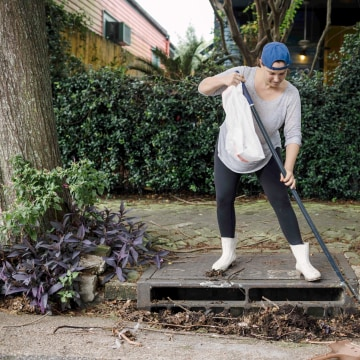 Image: Johnice Katz works to clear the storm drain in front of her home in preparation for Hurricane Nate in New Orleans on Oct. 07, 2017.