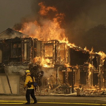 Image: A firefighters walks near a home in Santa Rosa