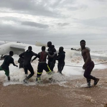 Image: Bystanders pull the wreckage of the French military cargo plane carrying out of the sea after the crash near Abidjan.
