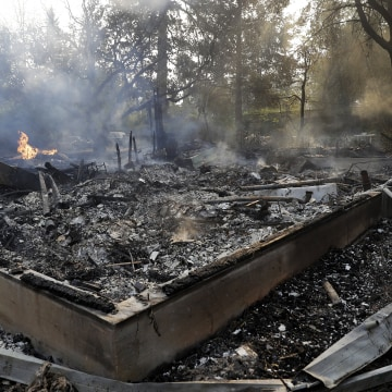 Image: Smoke smolders from a fire-ravaged home destroyed by a wildfire