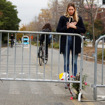 Image: Caroline Ventura looks down at flowers she laid for victims of Tuesday's attack outside a police barricade on the bike path next to West Street in New York City