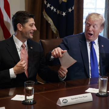 Image: Trump holds an example of what a new tax form may look like during a meeting