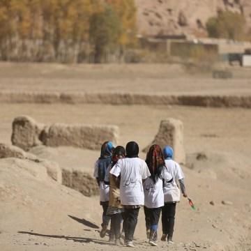 Image: Girls walk along a dirt road after running the Bamiyan Marathon
