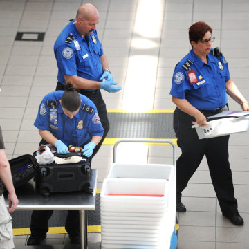 Image: A Transportation Security Administration (TSA) agent checks the luggage of a passenger