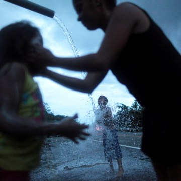 Image: A family bathe with mountain spring water after hurricane Maria hit the area in September, in Utuado