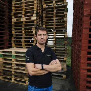 Image: Yumer Mustafa stands next to pallets used to transport fruit