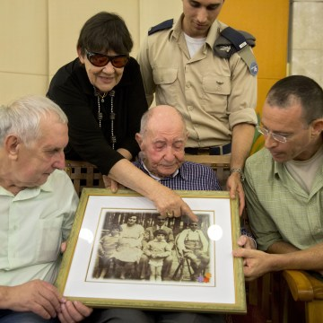 Image: Israeli Holocaust survivor Eliahu Pietruszka, center, looks at a picture with Alexandre Pietruszka and family in the central Israeli city of Kfar Saba on Nov. 16, 2017.